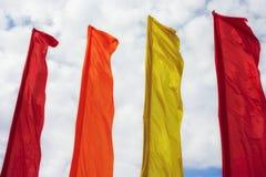 Fileira de bandeiras coloridas contra o céu nebuloso Imagem de Stock
