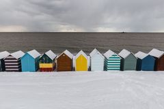 Fileira de cabanas da praia na neve do inverno na costa da baía de Herne, Kent, En fotografia de stock royalty free