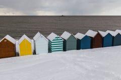 Fileira de cabanas da praia na neve do inverno na costa da baía de Herne, Kent, En fotografia de stock