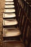 Fileira de cadeiras de madeira velhas Fotografia de Stock Royalty Free