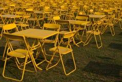 Fileira de cadeiras e de tabelas do metal amarelo na abundância foto de stock