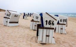 Fileira de cadeiras de praia de vime telhadas em uma paisagem da duna Localizado em auf Sylt de Hörnum, Schleswig-Holstein, Alem imagem de stock