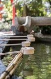 Fileira de copos cerimoniais da água no santuário de Yasui Konpiragu em Kyoto Imagens de Stock Royalty Free