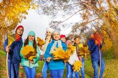 Fileira de crianças felizes com grupos dos ancinhos e das folhas Foto de Stock Royalty Free