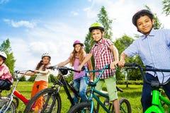 Fileira de crianças felizes em capacetes coloridos da bicicleta Imagens de Stock