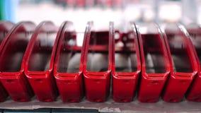 Fileira de detalhes do metal na cor vermelha após a pintura Boletos pintados na prateleira video estoque