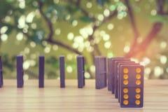 A fileira de dominós pretos velhos da cor com ponto colorido remenda no assoalho de madeira com as árvores verdes no fundo Imagens de Stock Royalty Free