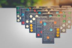 A fileira de dominós pretos velhos da cor com ponto colorido remenda no fundo branco do assoalho Fotografia de Stock Royalty Free