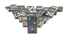 A fileira de dominós pretos velhos da cor com ponto colorido remenda no fundo branco do assoalho Fotos de Stock