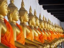 Fileira de est?tuas douradas da Buda no templo antigo arruinado imagens de stock