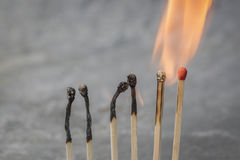 Fileira de fósforos ardentes Imagem de Stock