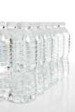 Fileira de garrafas de água plásticas no branco Imagens de Stock Royalty Free