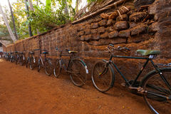 A fileira de India Bicycles a estrada de terra da parede de pedra Fotos de Stock