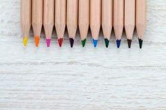 Fileira de lápis coloridos no fundo de madeira branco Fotos de Stock