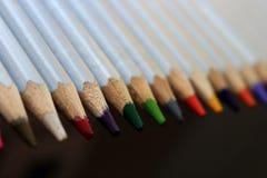 Fileira de lápis coloridos no fundo preto com perspectiva unfocused Conceito do desenho Pastéis isolados Fotografia de Stock Royalty Free
