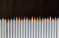 Fileira de lápis coloridos no fundo preto Conceito do desenho Pastéis isolados Arco-íris de lápis coloridos Escrevem o close up Foto de Stock Royalty Free