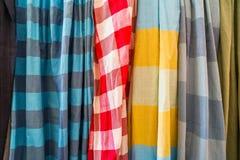 A fileira de lenços macios coloridos tradicionais do tecido de algodão na planície e o verificador modelam a venda na loja local fotografia de stock