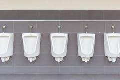 Fileira de mictórios exteriores na parede cinzenta no toalete público dos homens Imagens de Stock Royalty Free