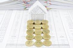 Fileira de moedas de ouro na frente da casa Fotos de Stock Royalty Free