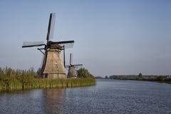 Fileira de moinhos de vento tradicionais ao longo do canal azul em Kinderdijk Foto de Stock Royalty Free