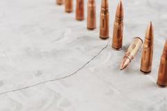 Fileira de muitas balas do metal e de uma bala caída no concreto quebrado cinzento imagem de stock