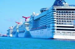 A fileira de navios de cruzeiros grandes no aqua coloriu a água Fotografia de Stock Royalty Free