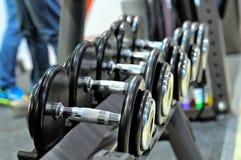 Fileira de pesos do metal na cremalheira no gym, clube de esporte Fotografia de Stock