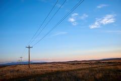 Fileira de polos da eletricidade com cabos de alta tensão foto de stock