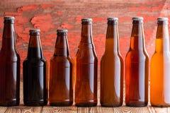 Fileira de sete tipos de cerveja em umas garrafas diferentes imagem de stock