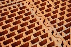 Fileira de tijolos na cor vermelha com os furos internos na forma do favo de mel no canteiro de obras Foto de Stock Royalty Free