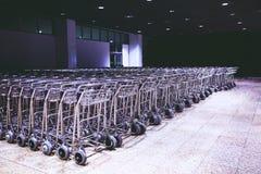 Fileira de troles dos carros da bagagem grande quantidade no aeroporto moderno internacional fotos de stock royalty free