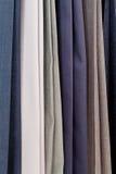 Fileira de várias calças de lã em costurar a oficina Fotografia de Stock