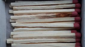 Fileira de varas do fósforo com cabeças vermelhas Os fósforos principais vermelhos em um branco abriram a caixa no fundo branco imagem de stock