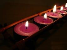 Fileira de velas cor-de-rosa na escuridão fotografia de stock royalty free