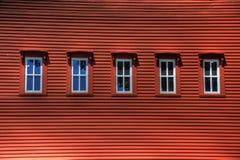 Fileira de Windows no edifício vermelho Imagens de Stock
