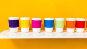 Fileira do copo cerâmico branco com o copo colorido do silicone do pantone Imagens de Stock Royalty Free