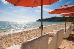 A fileira do guarda-chuva alaranjado e a praia branca bench na luz brilhante Foto de Stock