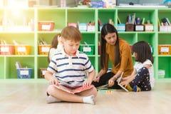 Fileira do livro de leitura elementar multi-étnico dos estudantes na sala de aula imagens do estilo do efeito do vintage imagem de stock