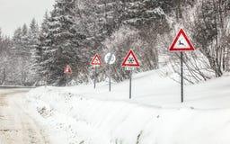 Fileira do roadsign de advertência na peça perigosa da estrada de floresta, durante o blizzard do inverno Cuidado - cervos, neve, foto de stock