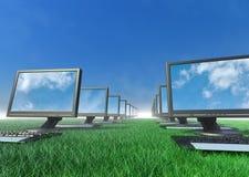 Fileira dos computadores em um campo da grama. Imagens de Stock Royalty Free