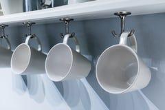 Fileira dos copos cerâmicos brancos que penduram no gancho de prata do metal sob o whi Fotografia de Stock
