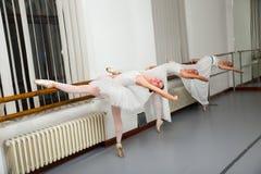 Fileira dos dançarinos de bailado que praticam na barra na sala do ensaio Foto de Stock
