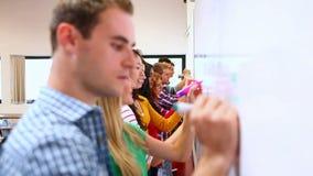 Fileira dos estudantes focalizados que escrevem no whiteboard na sala de aula video estoque