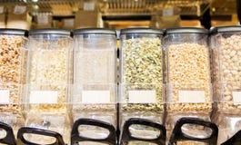 Fileira dos frascos com porcas e sementes na mercearia Imagens de Stock