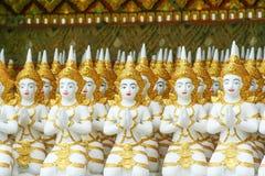 Fileira dos grupos lindos da estátua do anjo que sentam-se e para pressionar junto as mãos na caixa no templo imagens de stock royalty free