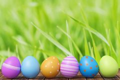 Fileira dos ovos da páscoa na grama com um fundo de madeira rendição 3d ilustração stock