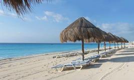 Fileira dos palapas e dos loungers na praia de cancun Fotografia de Stock