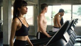 Fileira dos povos que exercitam em escadas rolantes no gym moderno Homens e mulheres da aptidão que dão certo junto video estoque