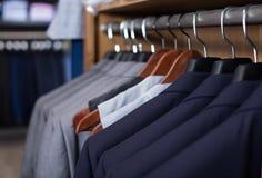 Fileira dos revestimentos em ganchos na loja de roupa dos homens imagens de stock royalty free