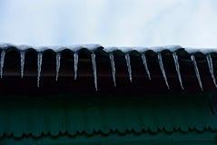 Fileira dos sincelos no telhado da casa contra a parede verde Foto de Stock